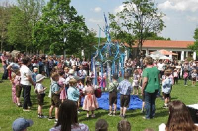 Kinder tanzen um den Maibaum